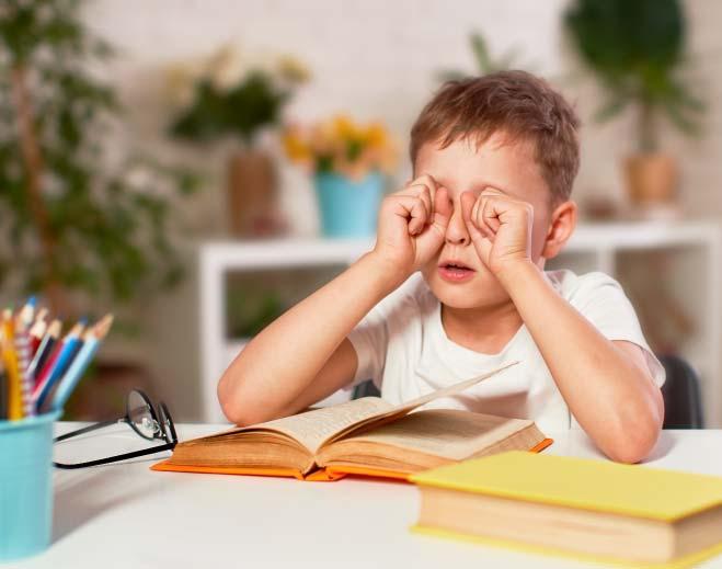 child rubbing eyes